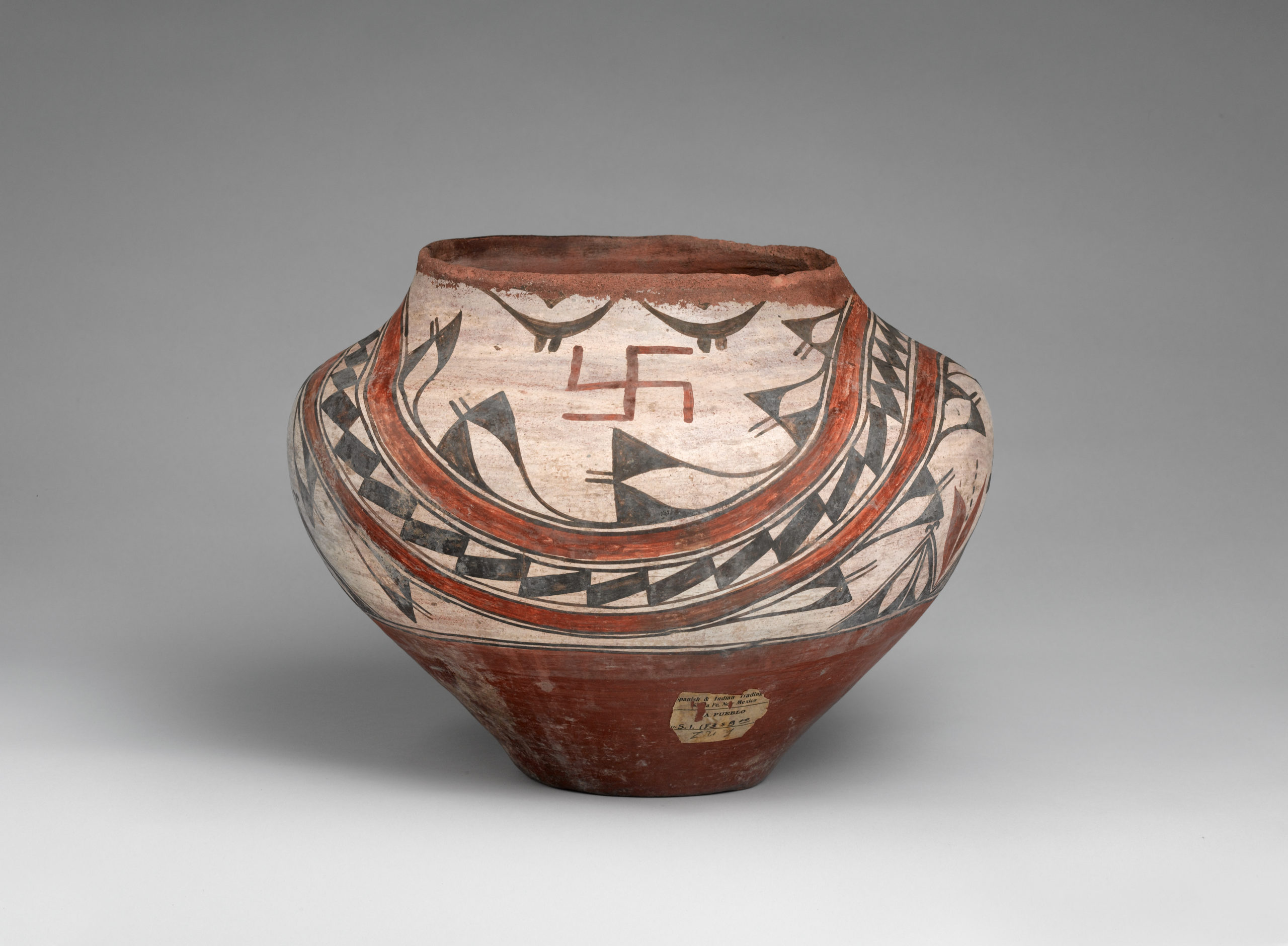 A Zia olla with an abstract design and two whirling log symbols painted in beige, brown, and black.