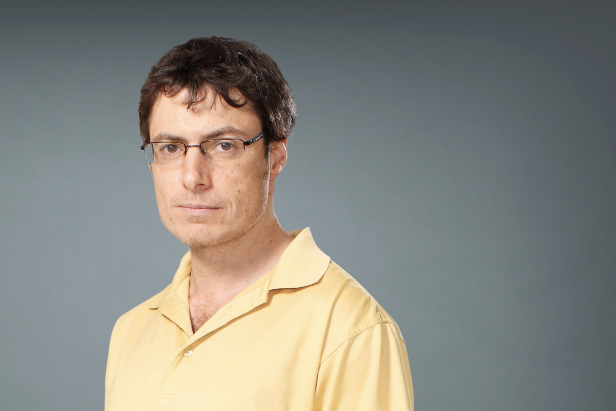 Evgeny Nudler, wearing a yellow polo shirt, in front of a neutral gray background.