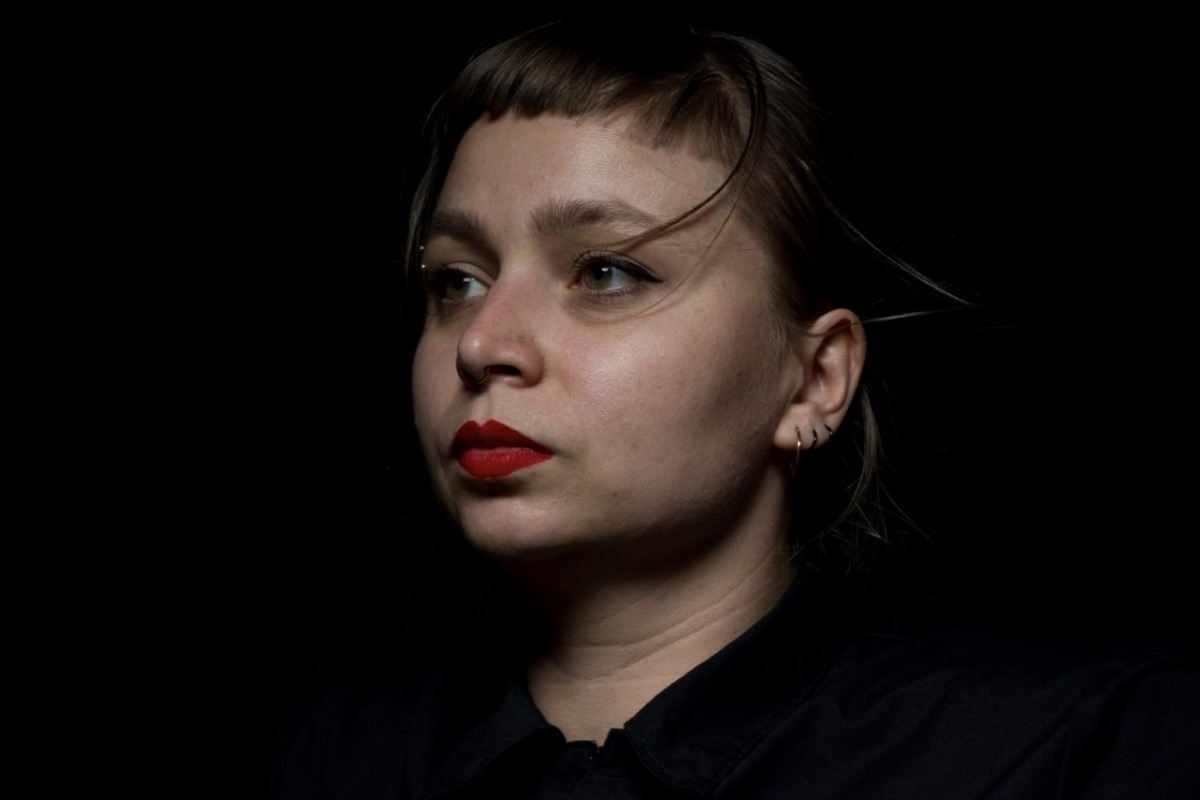 A photo of Alice Gosti against a black background, possibly in a theatre.