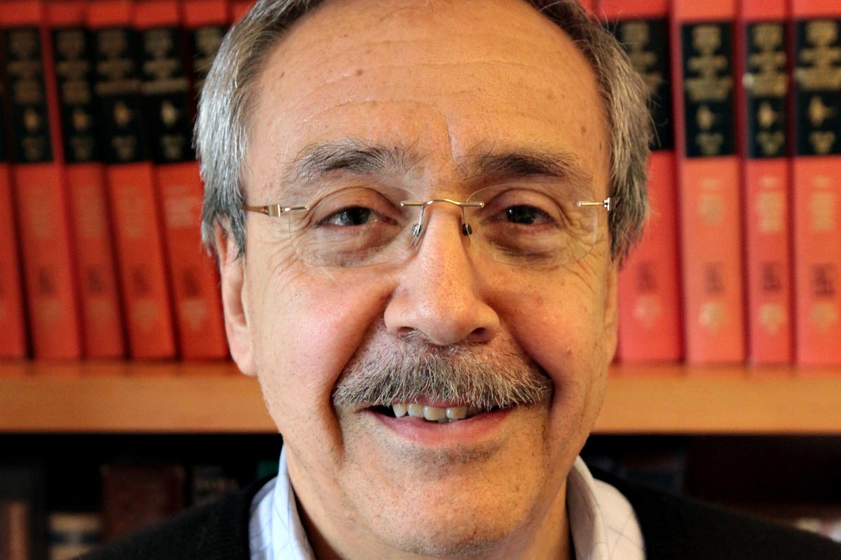A photo of Carlos Bustamante in front of a library shelf of scientific journals.