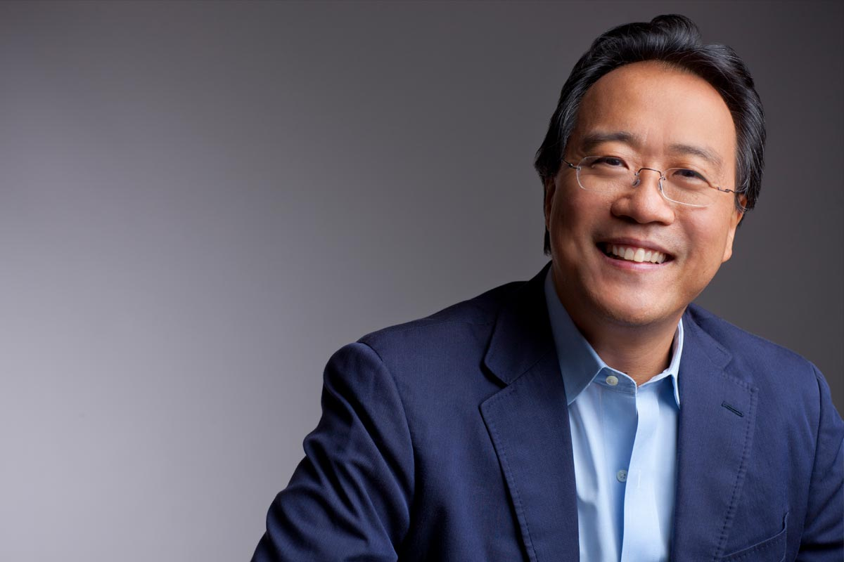 A photo of Yo-Yo Ma, wearing a blue dress shirt and jacket, against a gray neutral background.