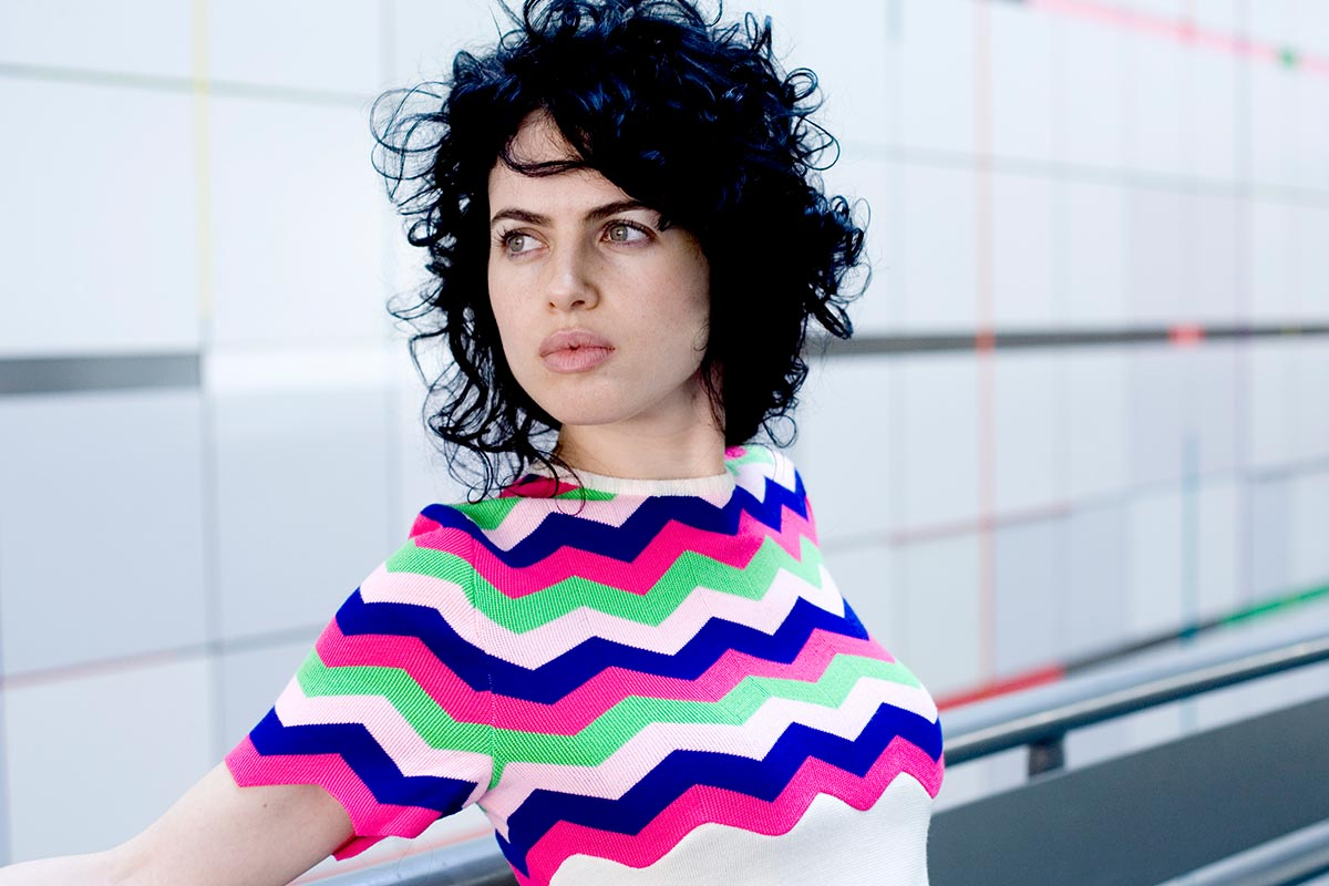 Neri Oxman in a striped blue, pink, green, and white shirt, looking away from the camera.