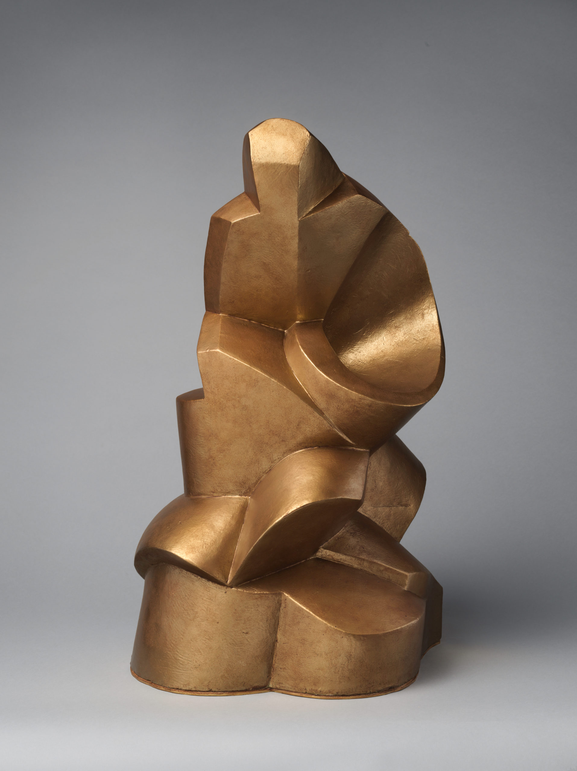 Gold sculpture of broad, cylindrical and flat-edged forms including a spiral.