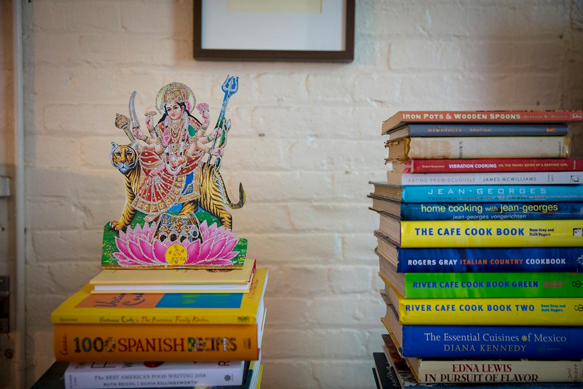 Tejal Rao's culinary books and personal effects on a shelf.