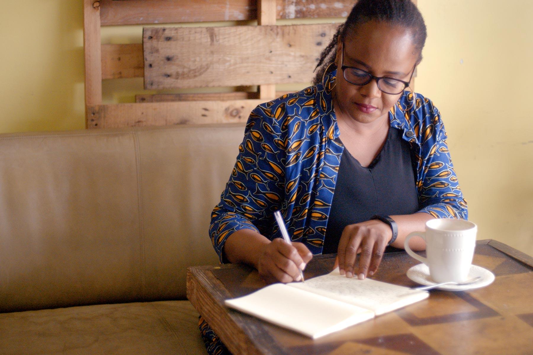 Edwidge Danticat writing in a notebook at a cafe.