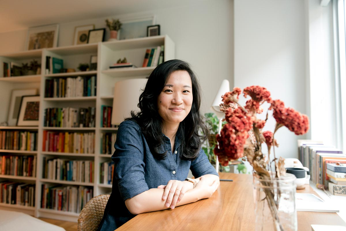 Jenny Xie sitting at a desk in front of a bookcase of literature in a light-filled room.