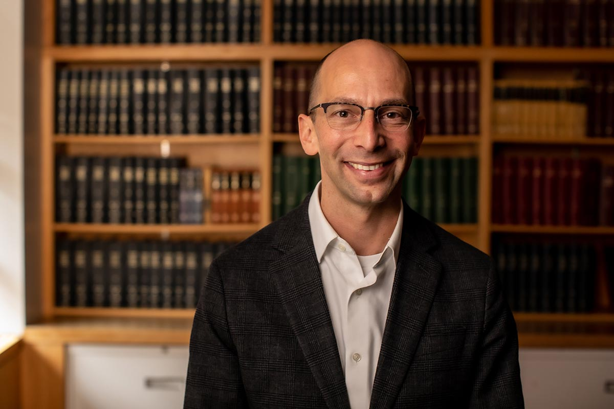 Portrait of Martin Jonikas, in suit jacket, in front of a library shelf of medical journals.