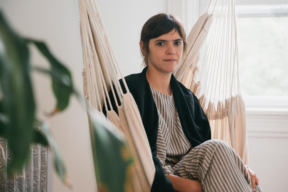 Vilcek Prize for Creative Promise winner Valeria Luiselli sitting on a hanging chair in her home in New York.