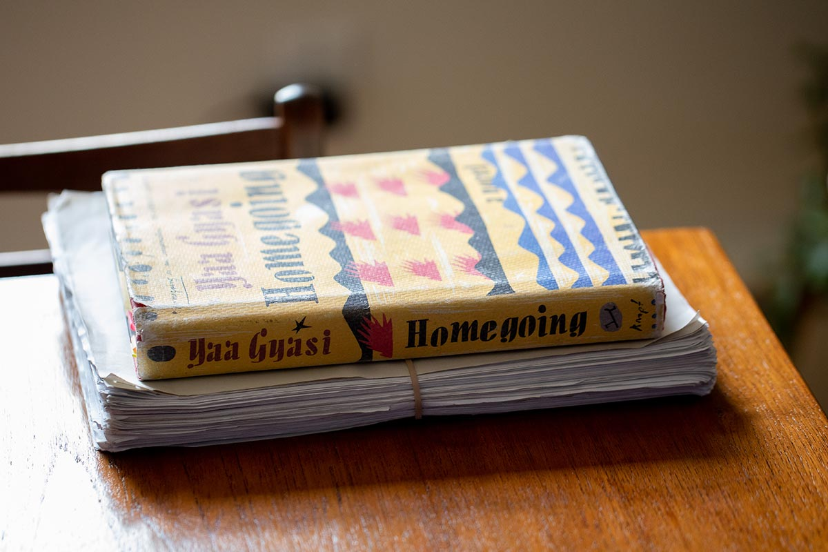"Author Yaa Gyasi's novel ""Homegoing"" sitting atop the original manuscript."