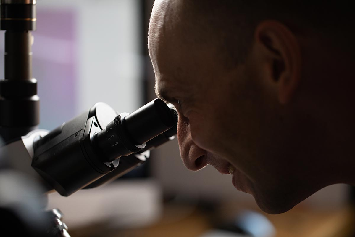 Martin Jonikas looking through a microscope.