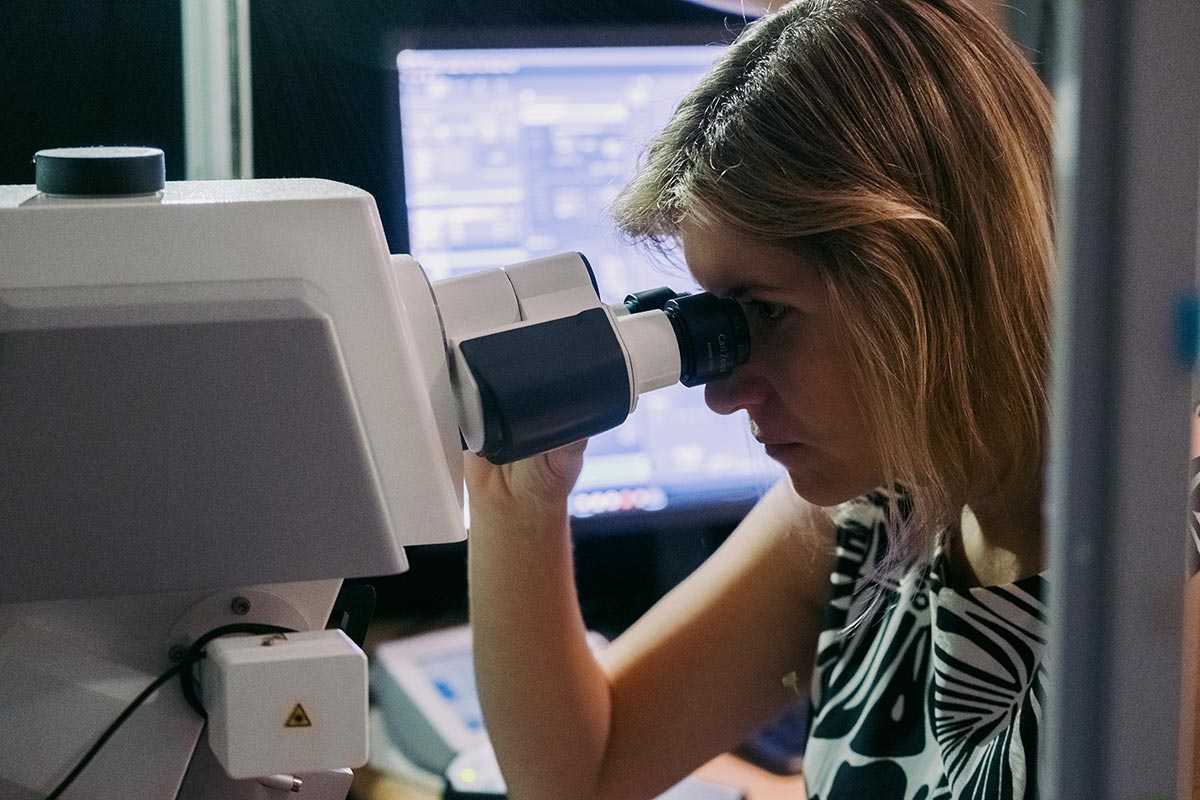 Viviana Gradinaru looking through a microscope.