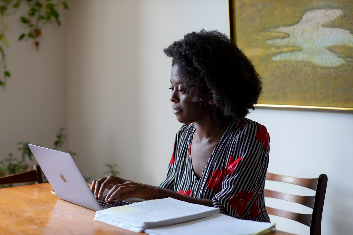 Yaa Gyasi typing on a laptop with novel manuscripts by her side.
