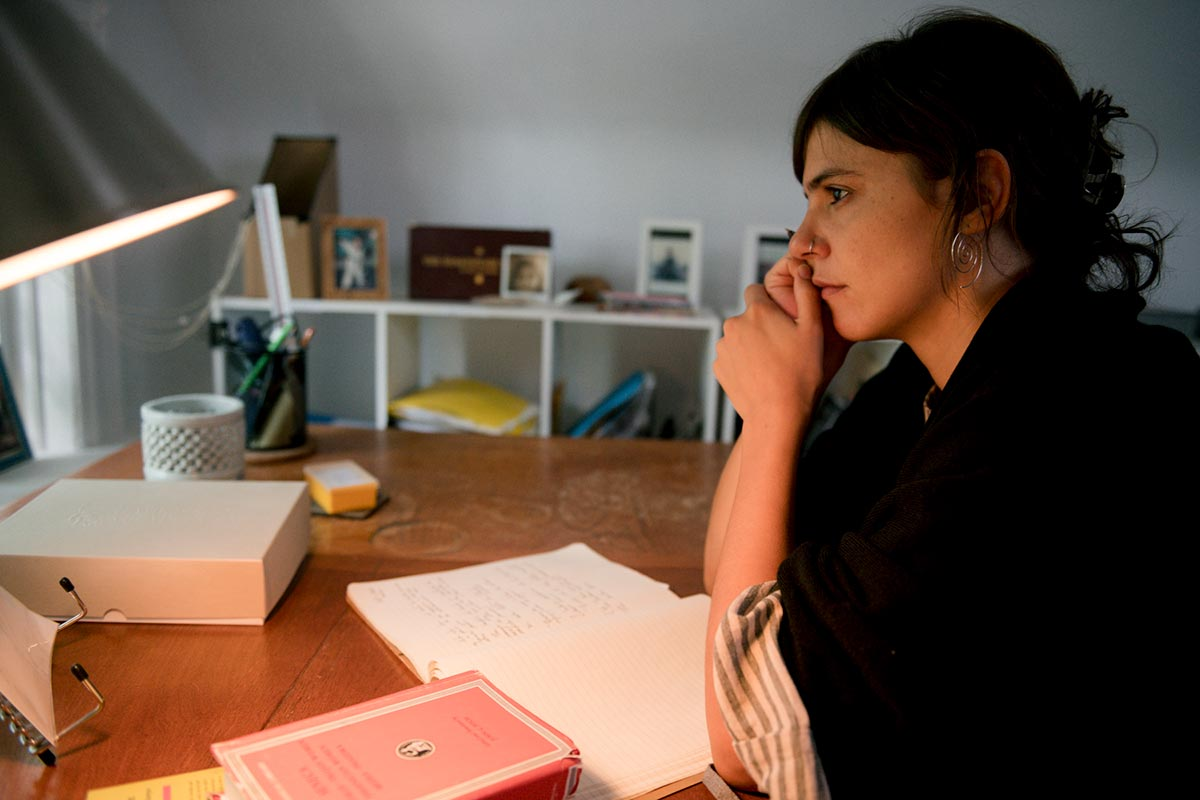 Valeria Luiselli writing at a desk.