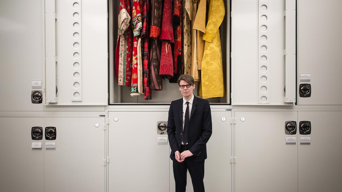 Andrew Bolton stands in front of a locker containing garments made of red and yellow silk, wearing a black suit and tie.