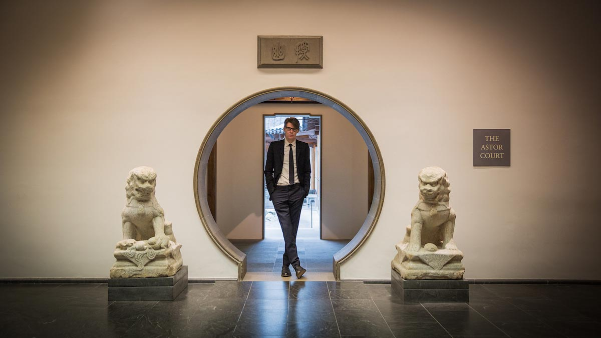Andrew Bolton, dressed in a suit, stands in the round entry way of the Astor Court, with two lion statues on each side.