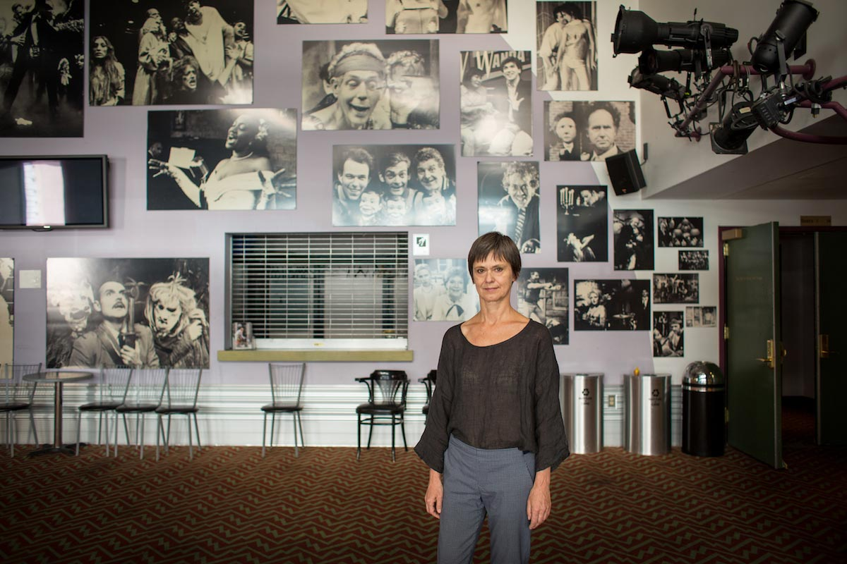 Blanka Zizka is pictured standing in the lobby of a theater, decorated with black and white images of famous actors throughout the ages.