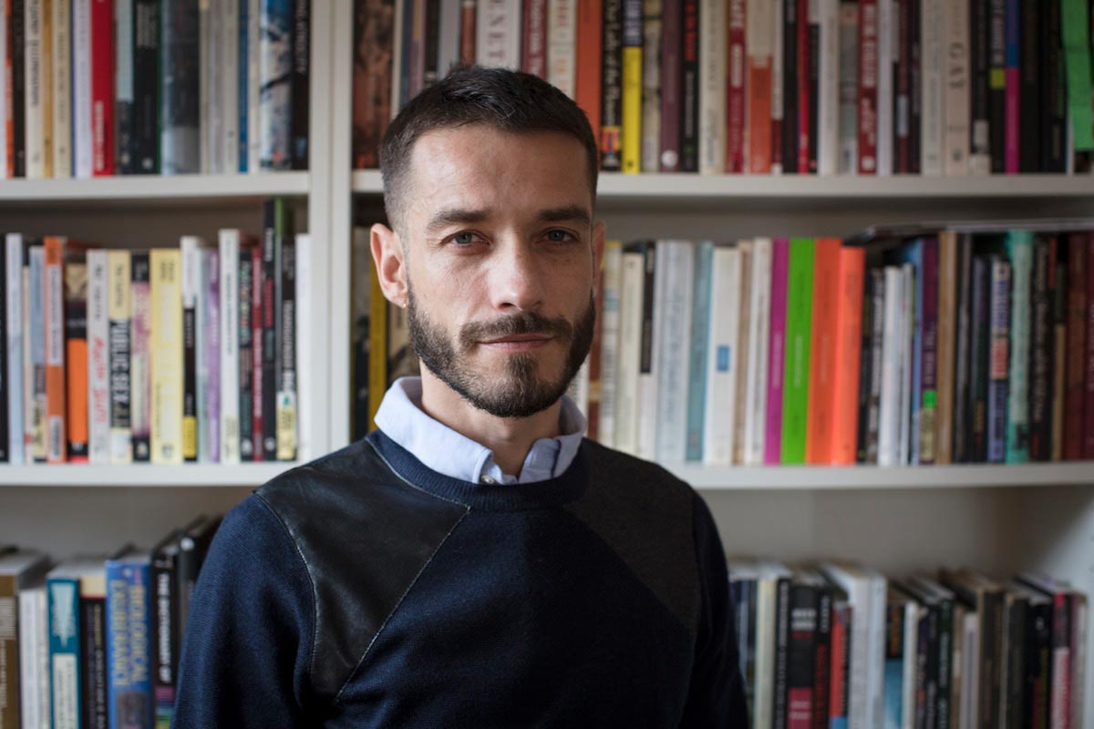 Carlos Motta is pictured from the chest-up in front of a bookshelf full of books.