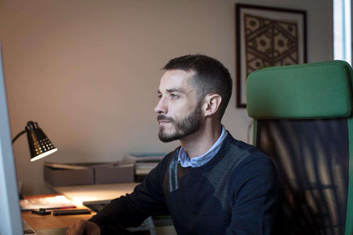 Carlos Motta in profile is pictured chest-up sitting in front of a computer screen.