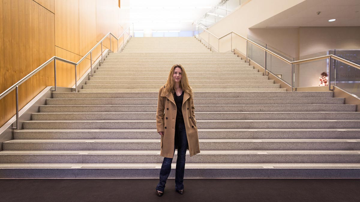 Franziska Michor stands at the foot of a large, wide staircase at a research facility, dressed in a trench coat.