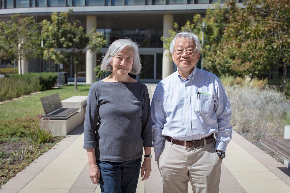 Lily and Yuh-Nung Jan stand on the plant-lined path outside of their research facility.