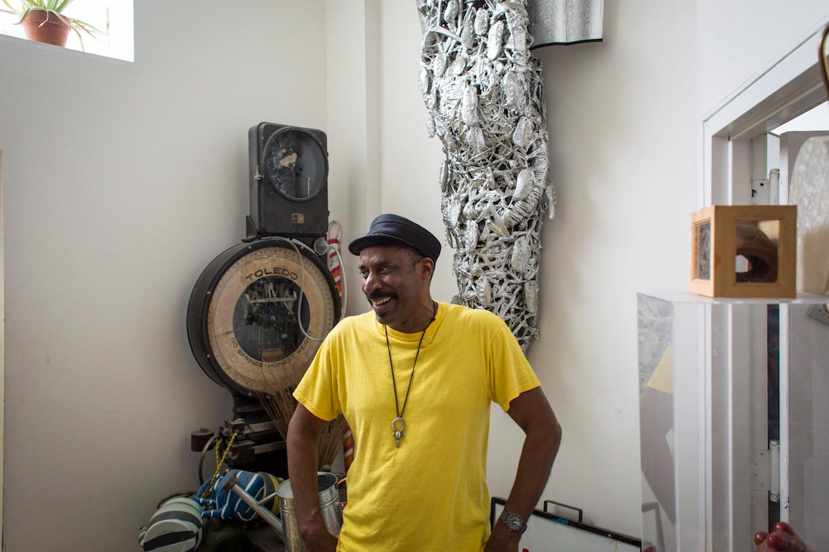 Nari Ward is pictured from the waist-up wearing a yellow shirt, smiling and looking off to the side, with his artworks behind him.