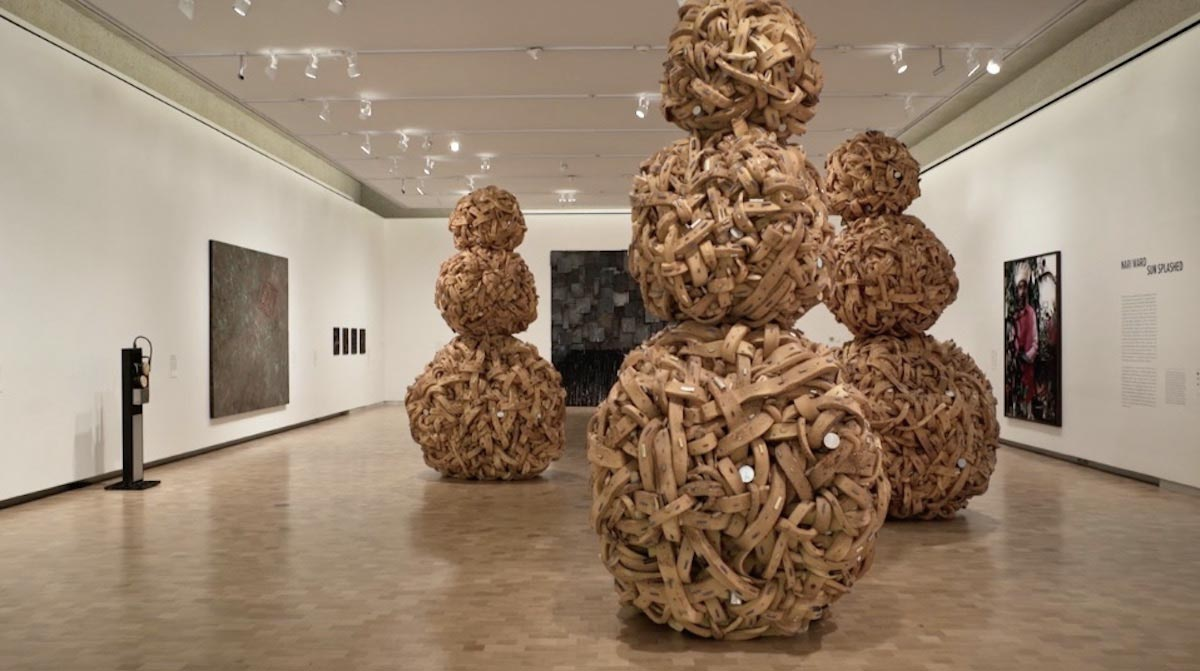 Three large art-pieces each consisting of three large balls stacked atop one another, stand on the floor of a gallery space with other artworks hanging on the walls.