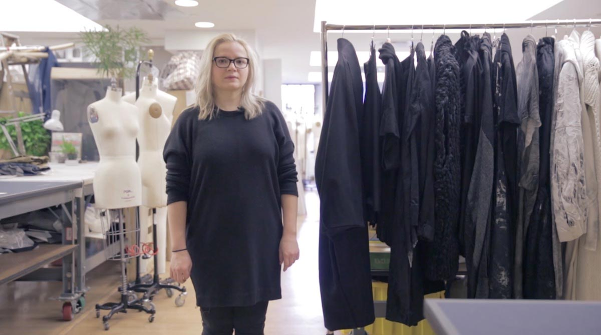 Natallia Pilipenka is pictured standing in a work space alongside a clothing rack and hanging garments, with mannequins and fabric behind her.