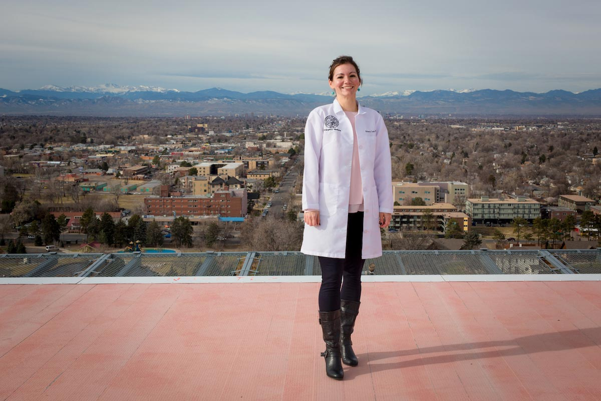 Roberta Capp is pictured standing on a rooftop with a picturesque view of the city and the Rocky Mountains behind her.