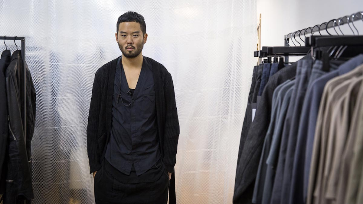Siki Im, dressed in a long black sweater, stands alongside garments hanging on clothing racks.