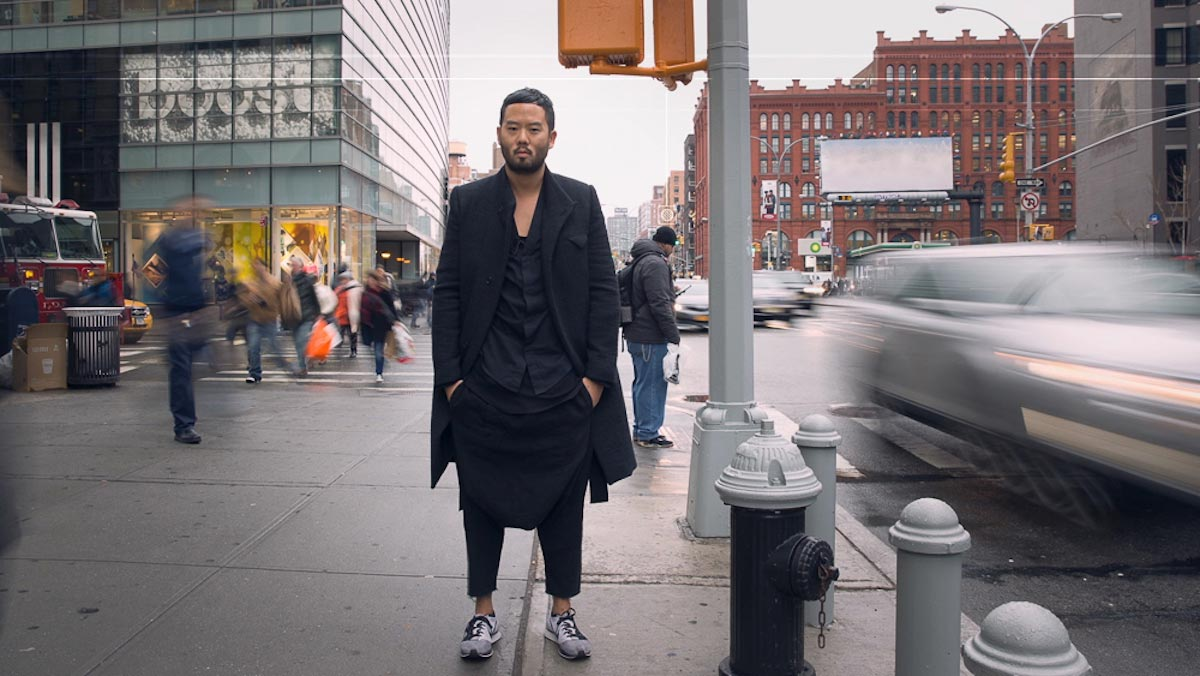 Siki Im, wearing a long black coat, stands on the bustling corner of two New York City streets.