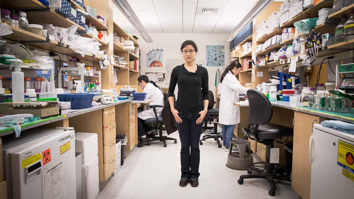 Sun Hur stands on the floor of a laboratory surrounded by lab apparatus and equipment.