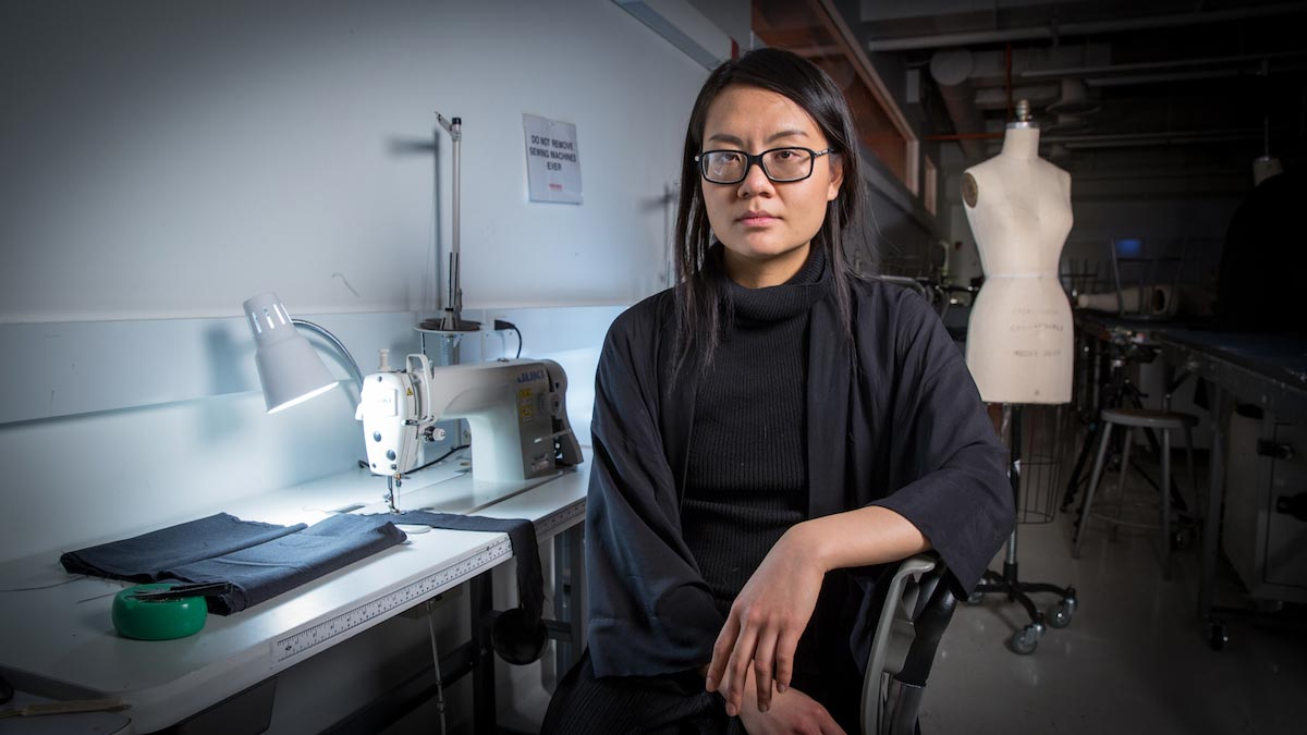 Tuyen Tran sits in front of a sewing machine, wearing a black sweater and glasses, with a mannequin in the background.