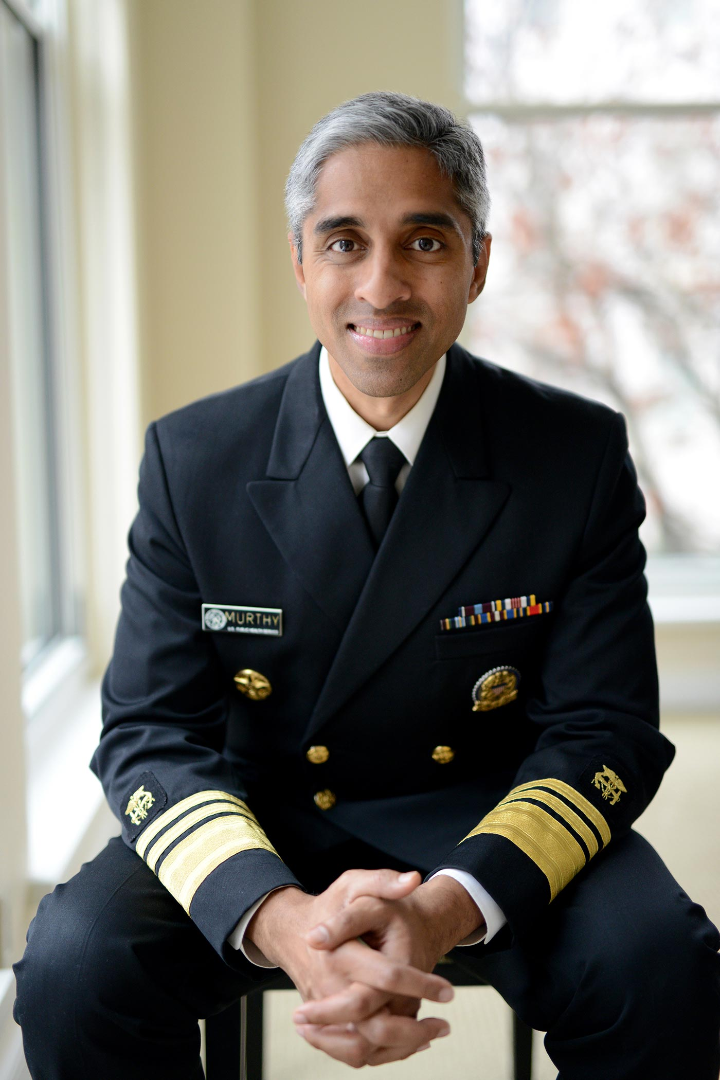 Vivek Murthy sitting on a chair, with collapsed hands, wearing surgeon general uniform.