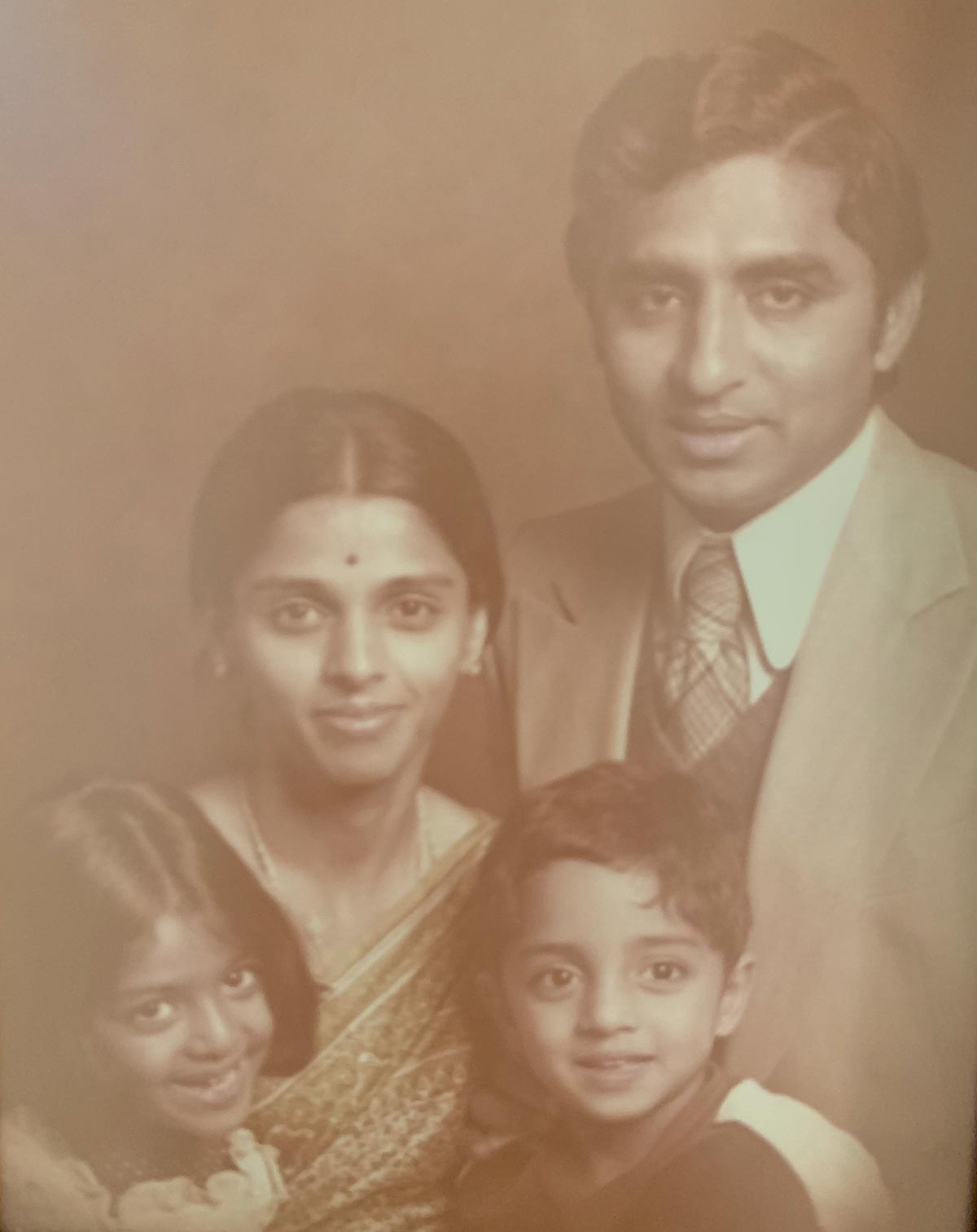 A sepia-tone photograph of Vivek Murthy as a child with his family.