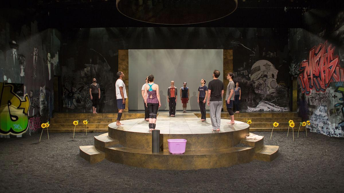 """The cast of the Wilma Theater's """"Rosencrantz and Guildenstern Are Dead"""" (2015) as they stand dispersed across a stage and a circular platform with graffiti painted backdrops behind them."""