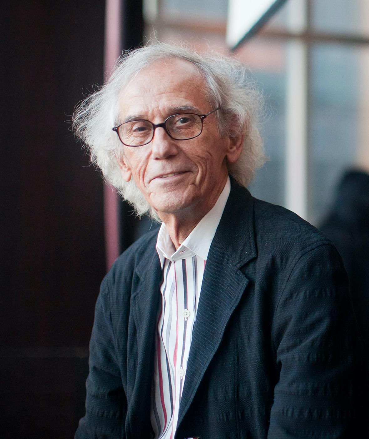 Christo standing in front of a wall of windows at the Mandarin Oriental in New York City.