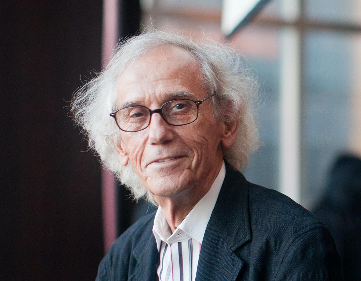 A photo of Christo in front of a wall of windows.
