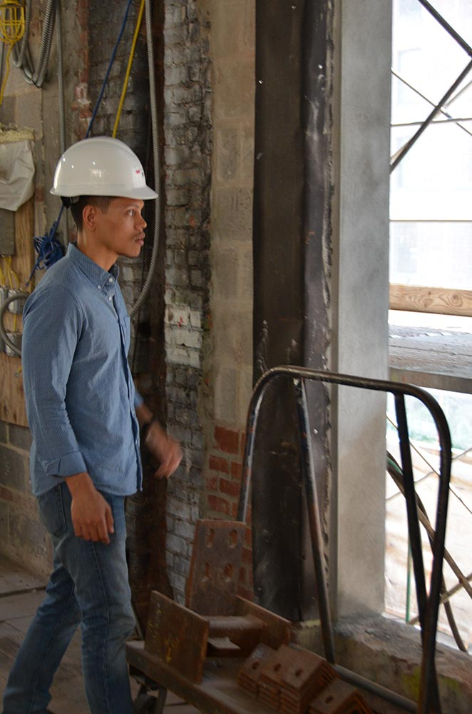 Ronnie Mewengkang, wearing a hard hat, surveying construction and window at the foundation's new headquarters.