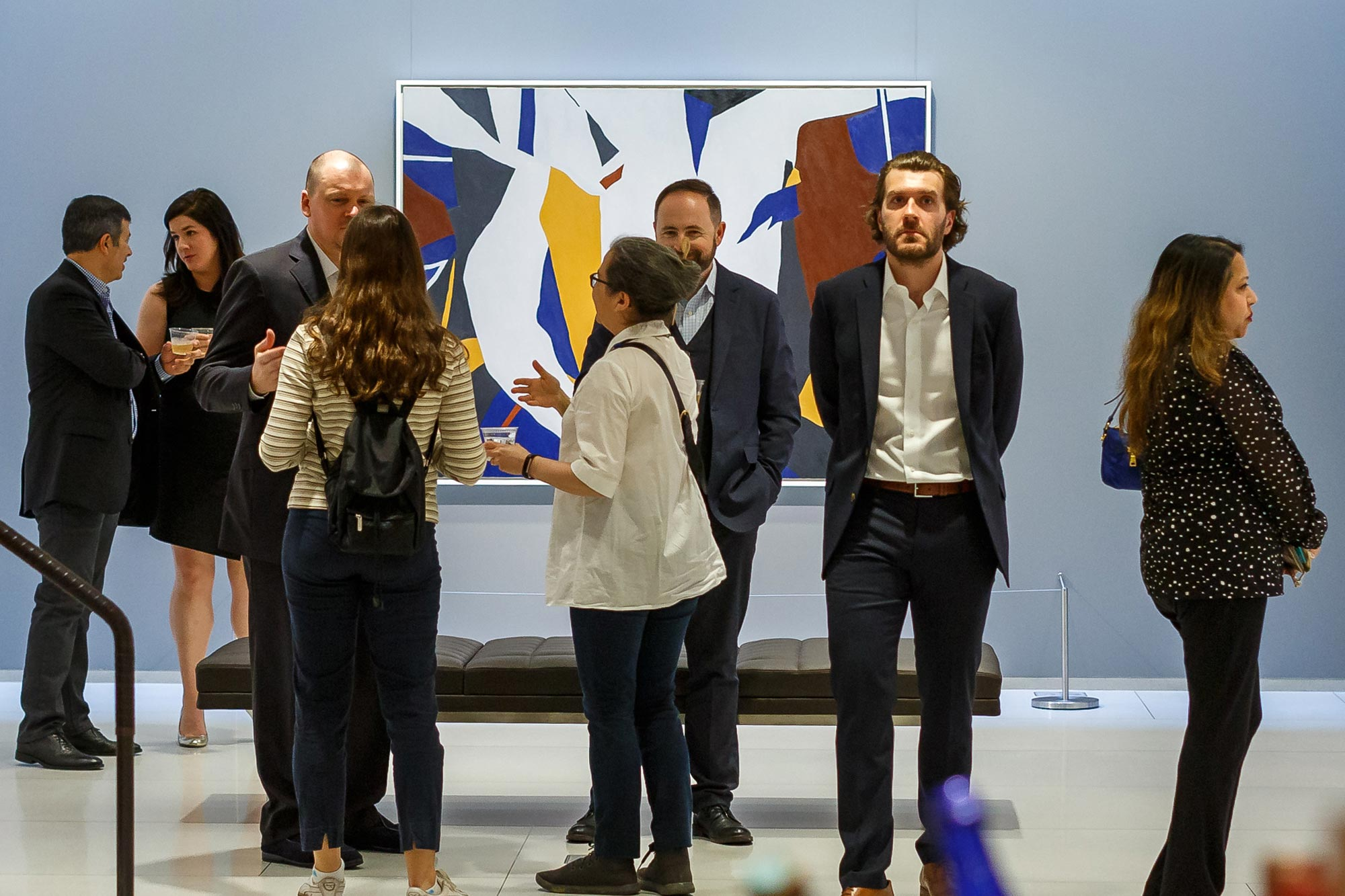 Seamus McKillop stands in a crowd of people at an opening reception of Ralston Crawford's work at the Vilcek Foundation.