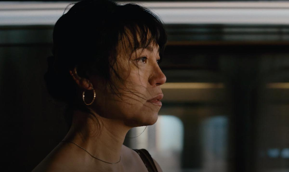 A close-up and side-profile of the protagonist in Lingua Franca, Olivia, with a subway train in the background.