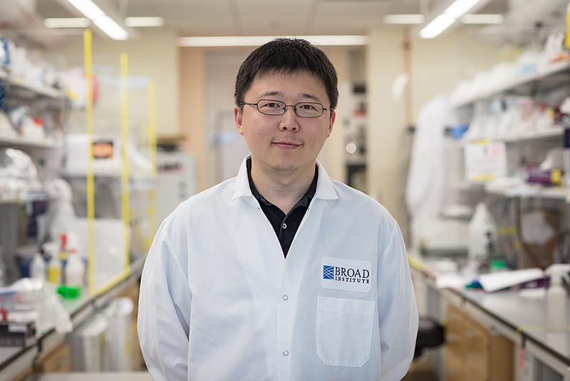 Feng Zhang is standing in an aisle in his lab, dressed in a white lab coat.