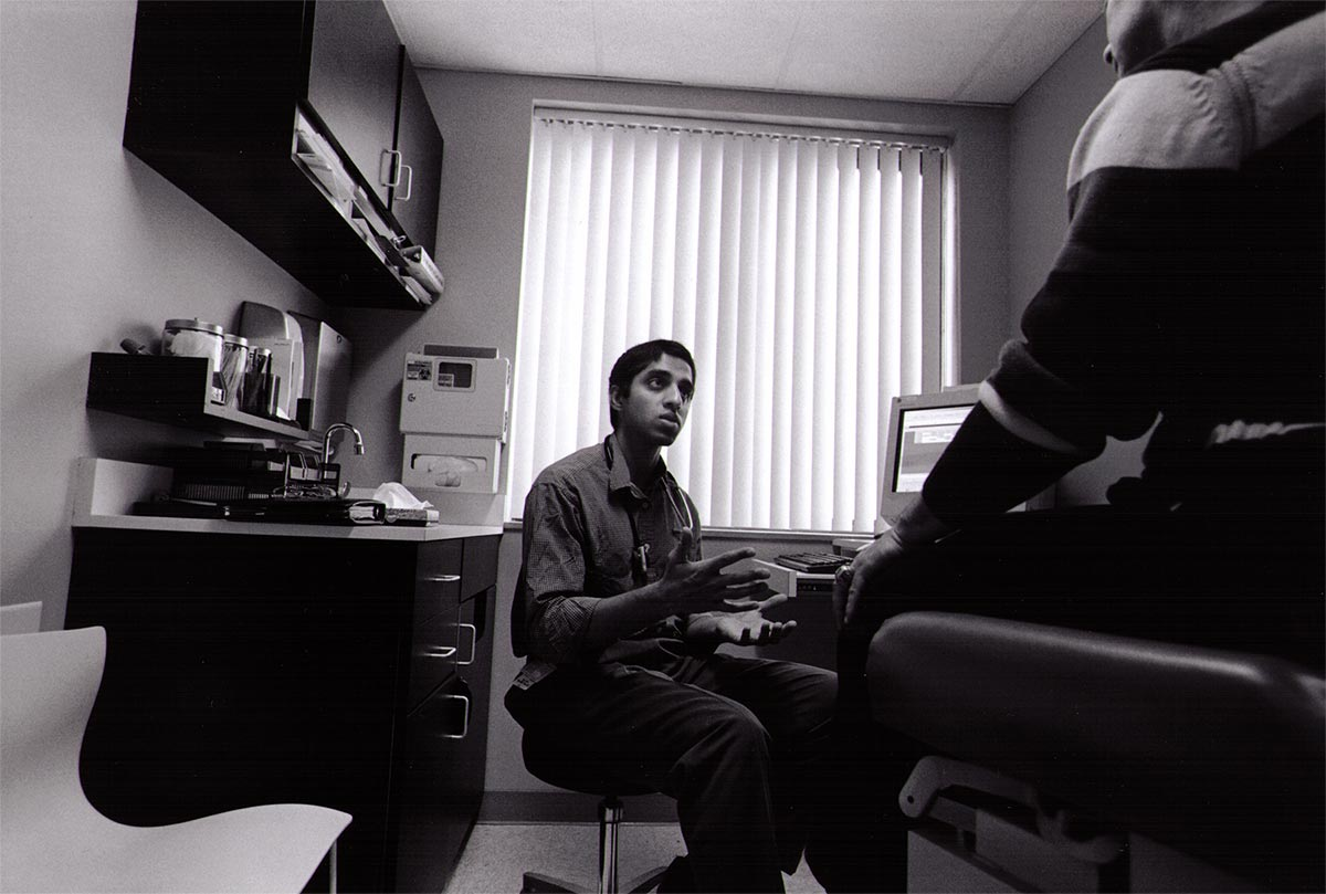 Black and white photograph of Vivek Murthy, sitting in a doctor's office, speaking to a patient.