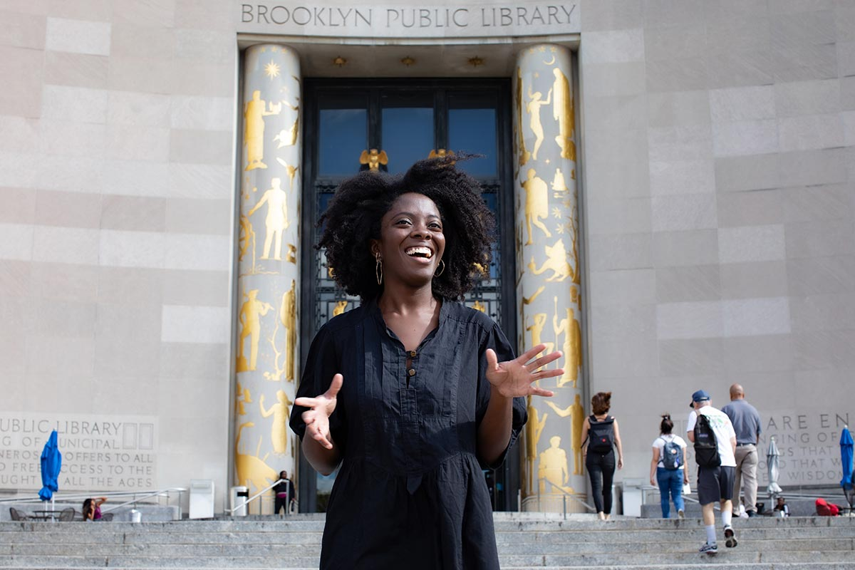 Yaa Gyasi standing on the steps of Brooklyn Public Library