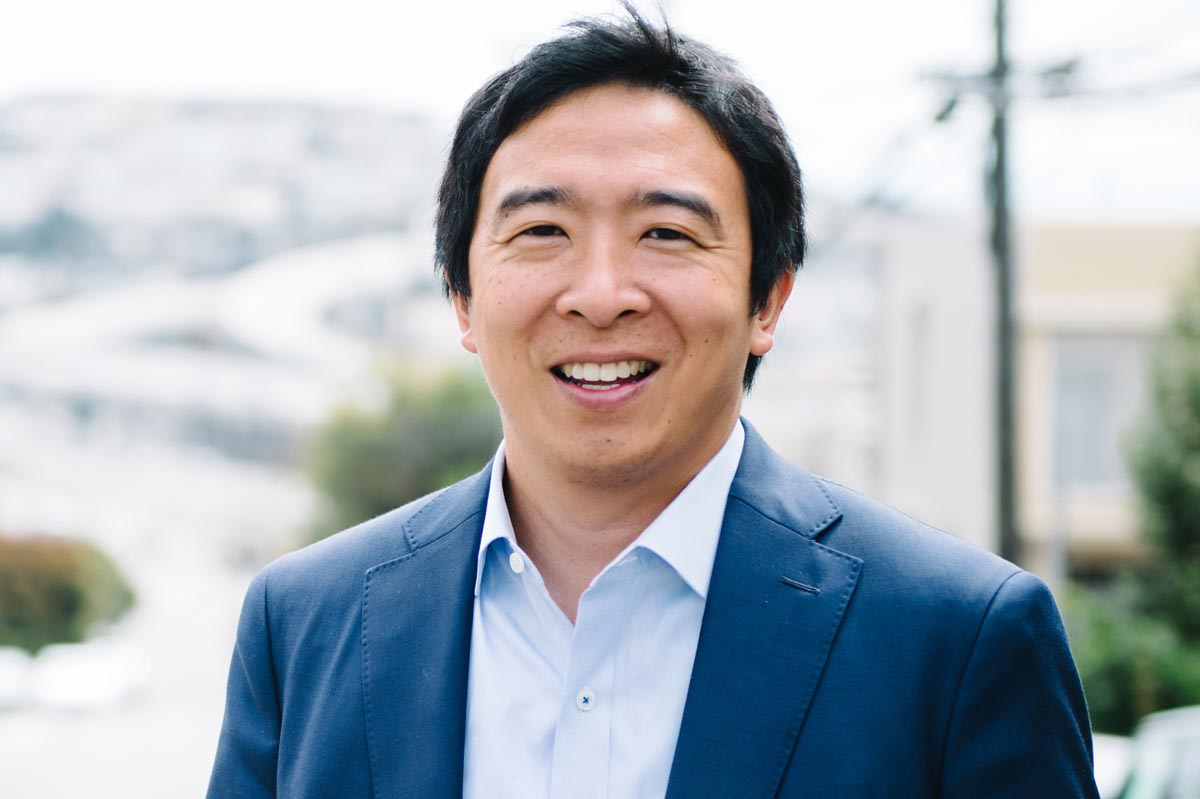 Andrew Yang, in a blue suit jacket and shirt, standing outside with a city in the background.