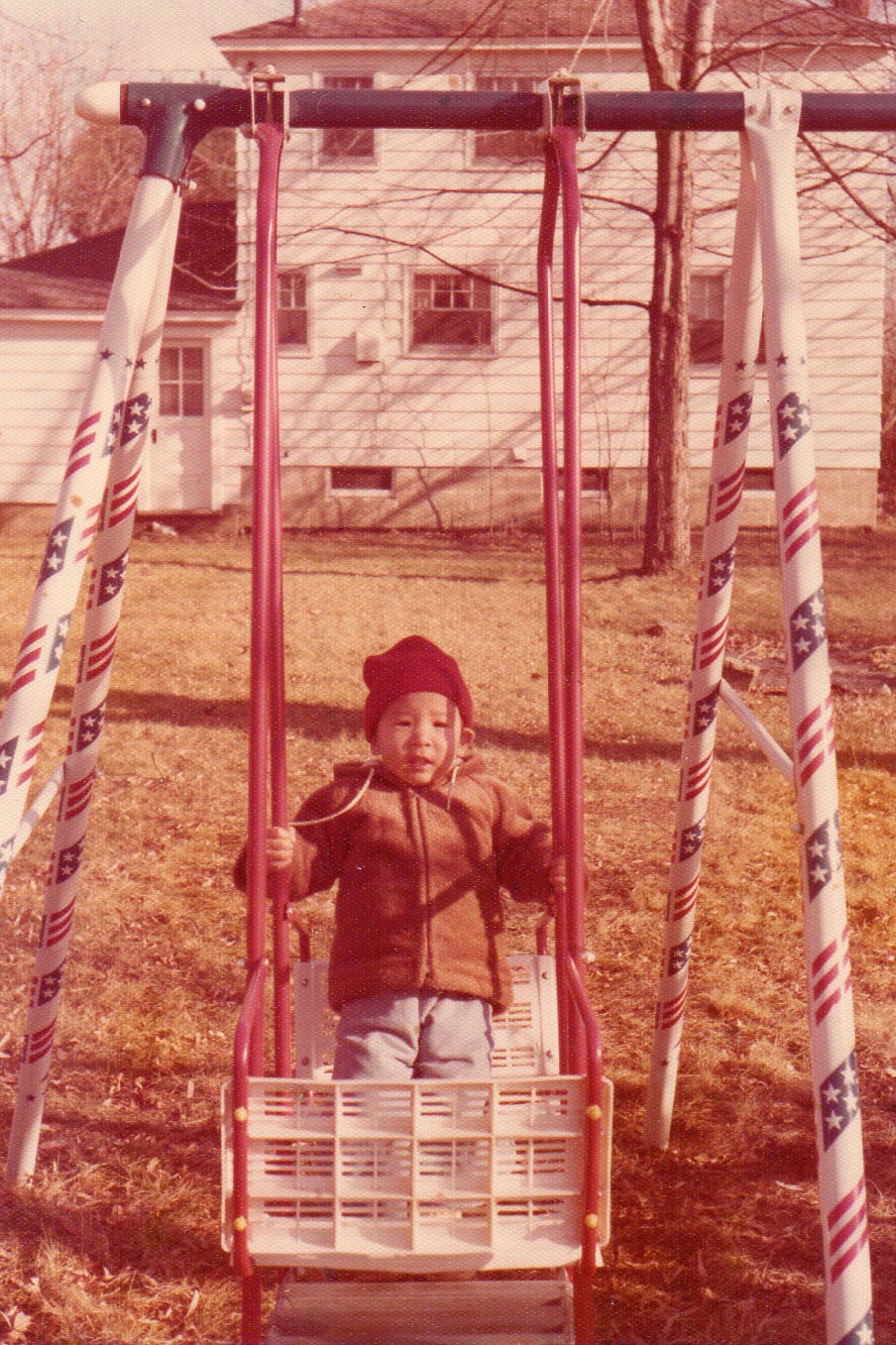 Andrew Yang, at age 2, sitting on a swing set in his home of upstate New York.