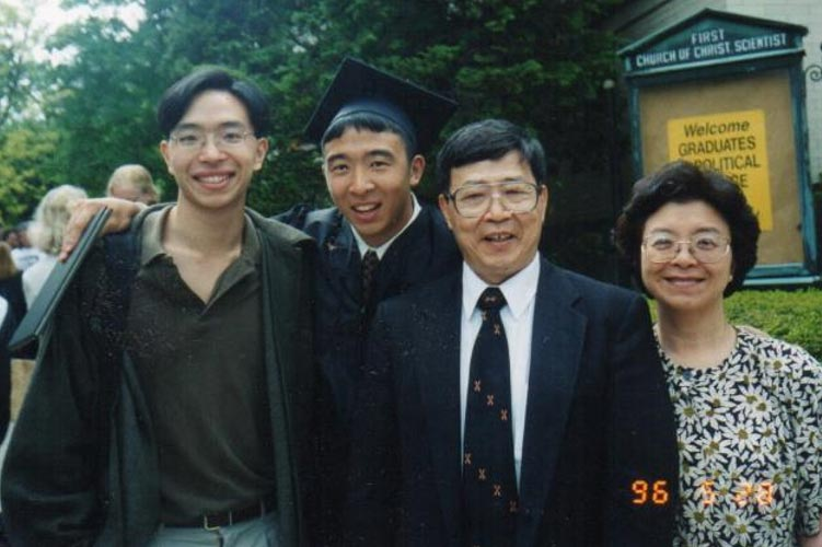 Andrew Yang, in graduation cap and gown, pictured with his brother, father, and mother.