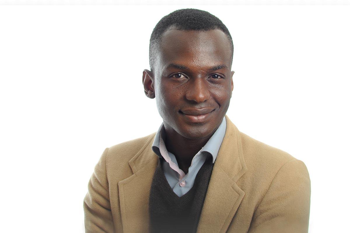 Ibrahim Cissé, wearing a tan suit, against a white backdrop.