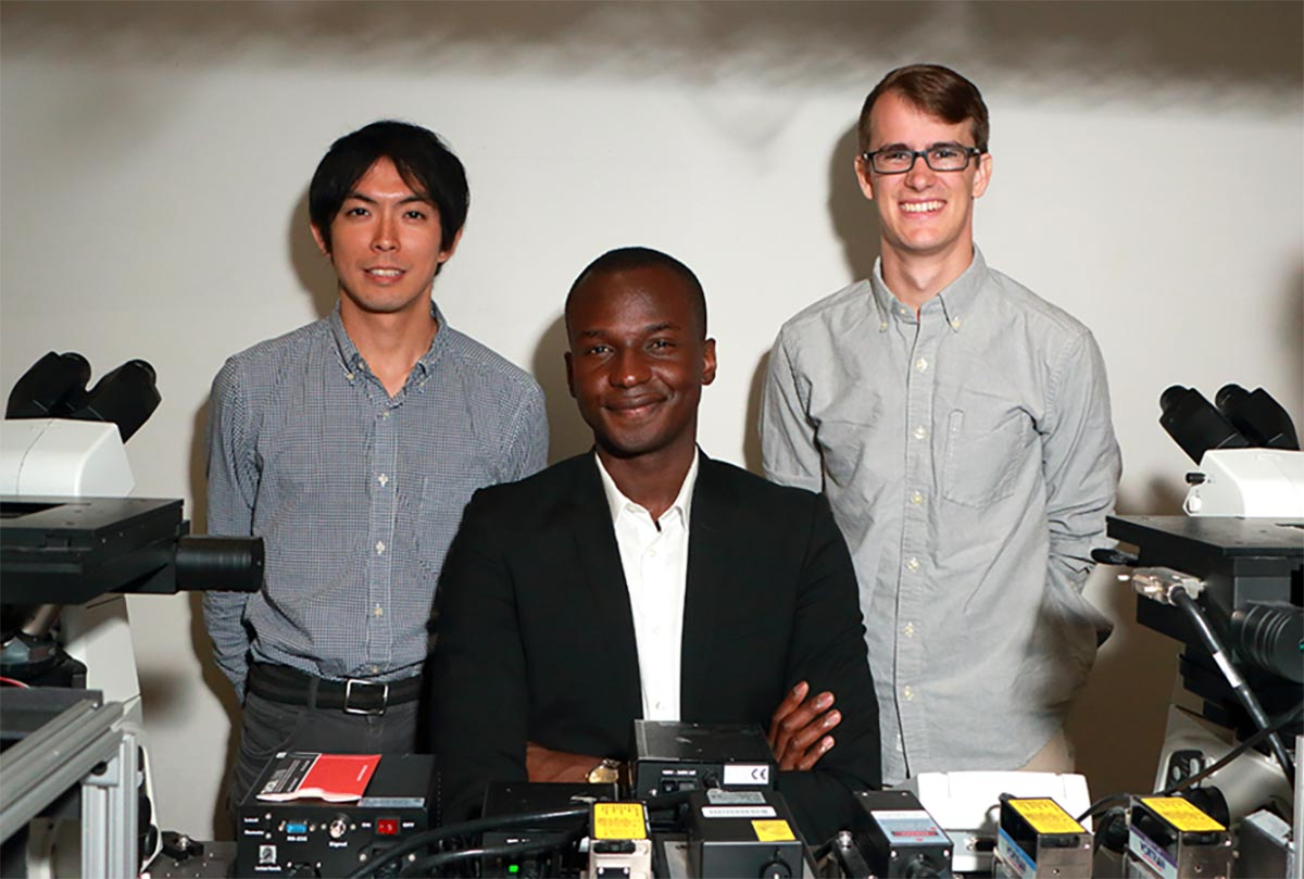 Ibrahim pictured with two graduate students on either side, with a table of microscopy and scientific equipment in front of them.