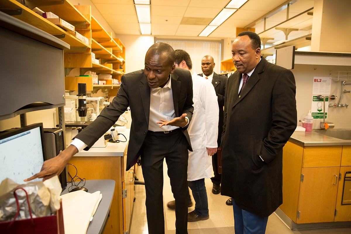 Ibrahim Cissé points to a computer to explain his research to Niger's President Mahamadou Issoufou.