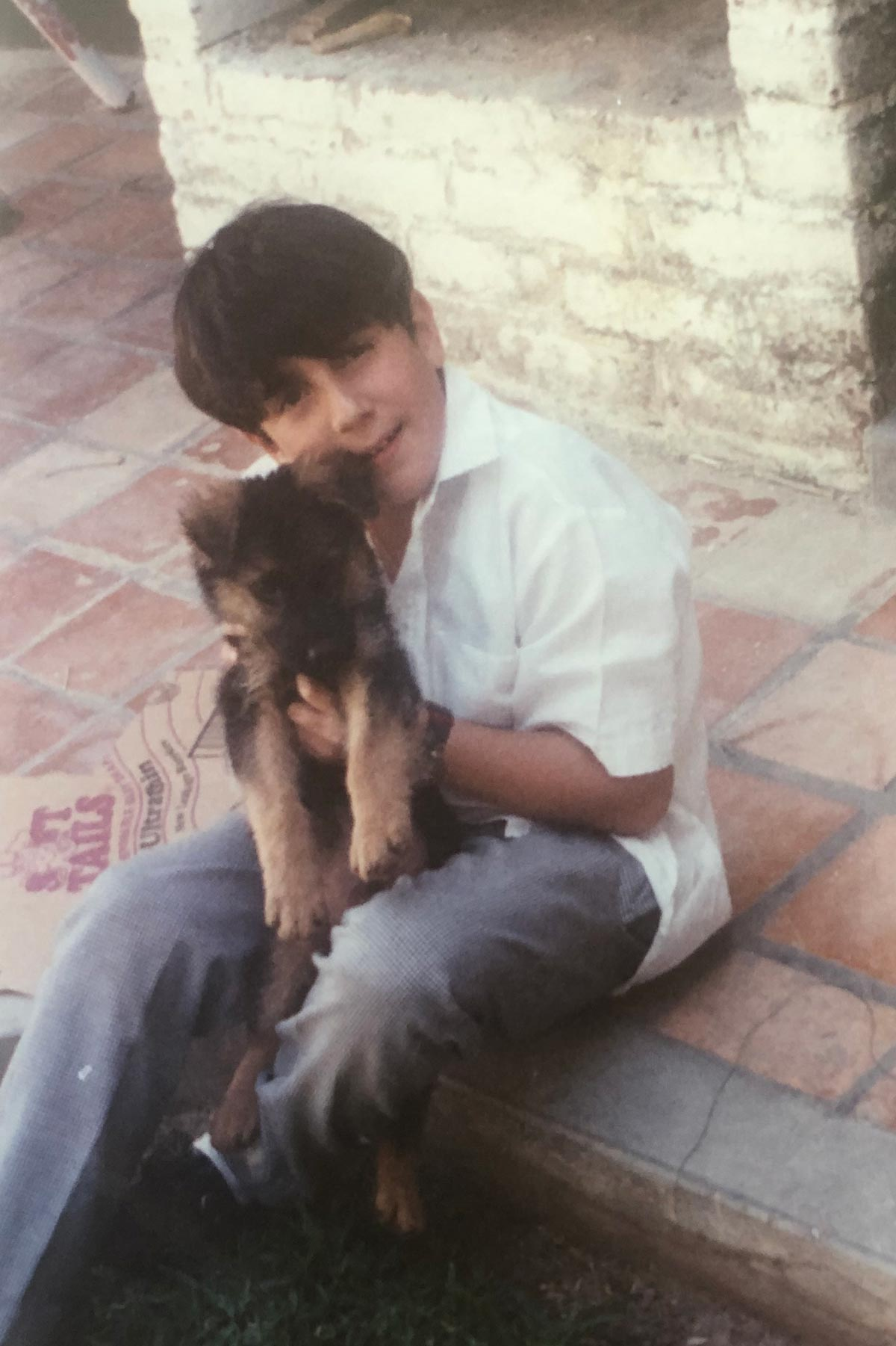 Juan Pablo González hugs a puppy outside on a patio.